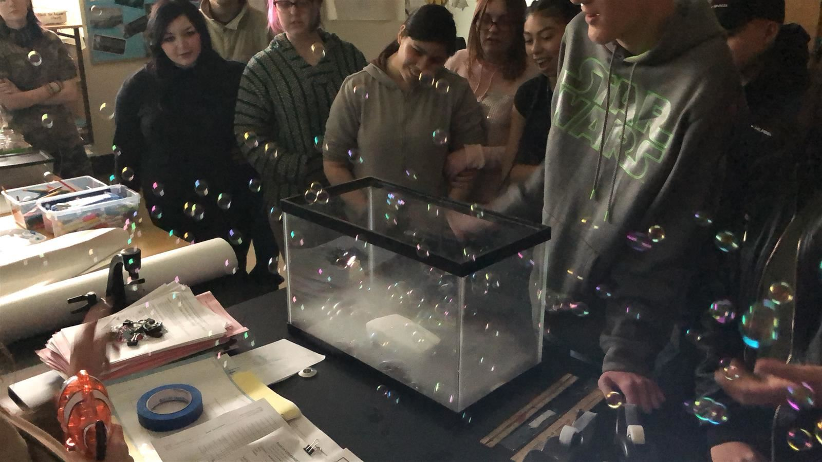 Students observe bubbles interacting with C02 in a study of space