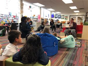 Students and parents listen intently to a story read by Ms. Horn.