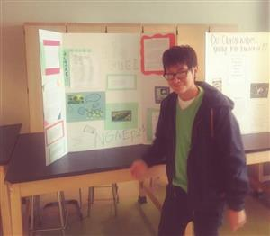 Student poses in front of his science fair board about bio-fuels.